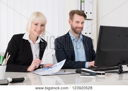 Two Businesspeople Using Computer For Analyzing Graph