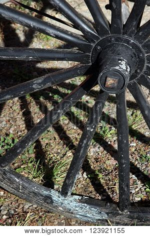 Spokes of an old wagon wheel casts shadows on the ground forming crisscross abstract still life