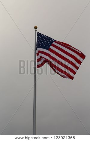 US flag on a pole waving in the wind ** Note: Visible grain at 100%, best at smaller sizes