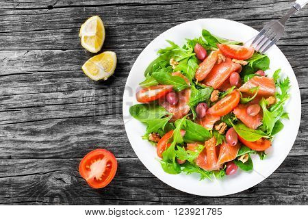 Red fish healthy salad with mixed lettuce leaves olives and tomatoes on a white dish on a old rustic table easy recipe top view