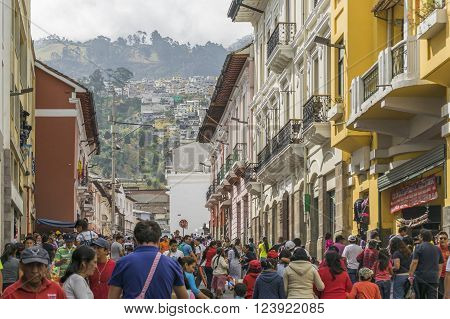 QUITO,  ECUADOR, OCTOBER - 2015 - Crowded sidewalk with colonial style buildings and hill at background in the historic center of Quito Ecuador.