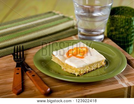Cornbread, pastel de choclo, a typical Peruvian dish served on green plate on wooden cutting board.