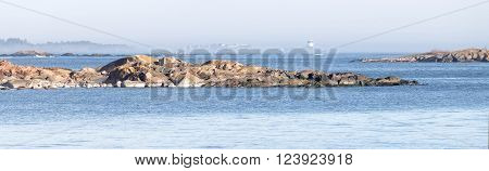 Panorama of coast, cliffs, islands and a distant beacon surrounded with fog a sunny day during spring time in scandinavia