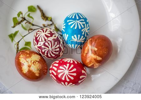 Homemade traditional decorated Eastern or Paschal eggs in white plate