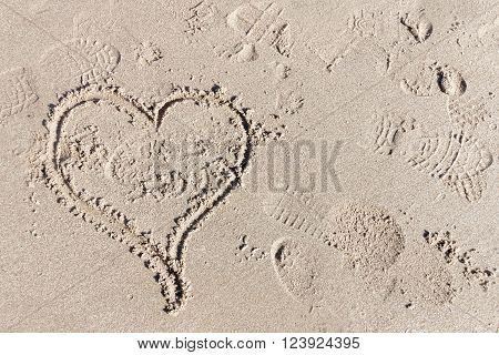 Heart in the sand, the symbol for love. Some foot prints