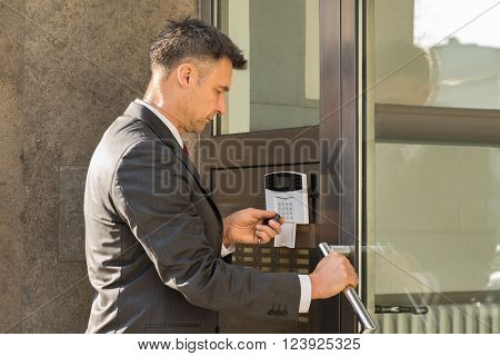 Close-up Of Businessman Using Remote Control For Operating Door Security System