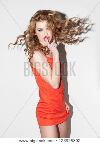Emotional young woman in a red dress. Shh Finger . Sign of silence . Angry Girl