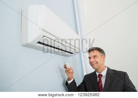 Businessman Using Remote Control To Operate Air Conditioner
