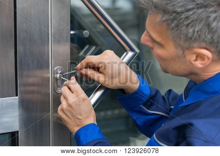 Mature Male Lockpicker Fixing Door Handle At Home