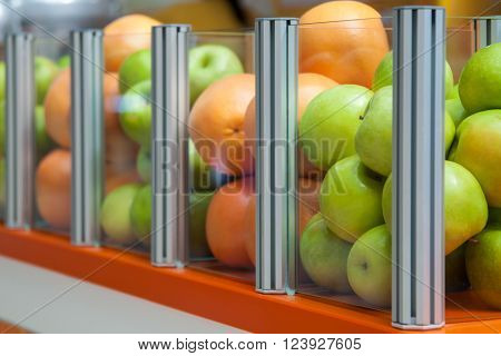 Glass Showcase With Fresh Fruit Apples And Oranges, Focus Is Positioned On Apples