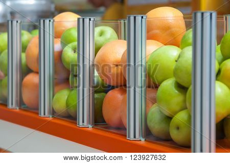 A Large Glass Container Showcase Fresh Fruit Apples And Oranges, Focus Is Positioned On Oranges