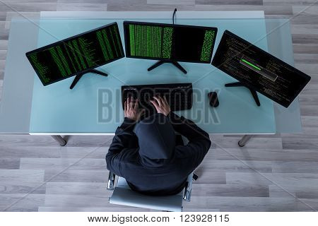 High Angle View Of Hacker Stealing Information From Multiple Computers
