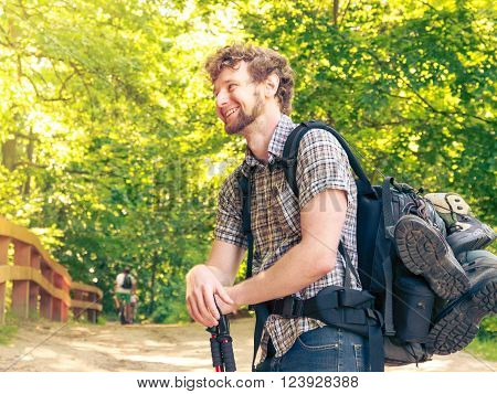 Adventure tourism enjoying summer time - young tourist man with backpack sticks hiking in forest trail ** Note: Visible grain at 100%, best at smaller sizes