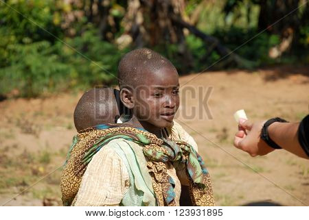 August 8 2015 Pomerini - Tanzania - Africa - Two unidentified African children a girl carrying a baby in towel receiving by a white volunteer a piece of sugar cane often only food available