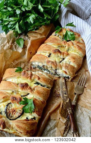 Vegetable pie with aubergine and spinach on the wooden background