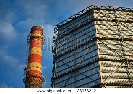 Industrial plant. Factory with a red pipe against blue sky