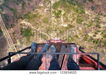 Urban explorers standing at the top of abandoned tower in army boots