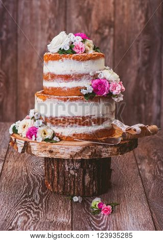 Homemade wedding naked cake  decorated with flowers on wooden cut stand