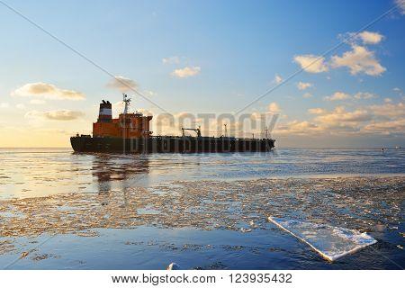 Cargo ship (bulk carrier) sailing in still frozen sea at beautiful sunset
