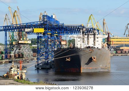 Cargo ship loading in Riga port. Industrial landscape with ships and cranes.