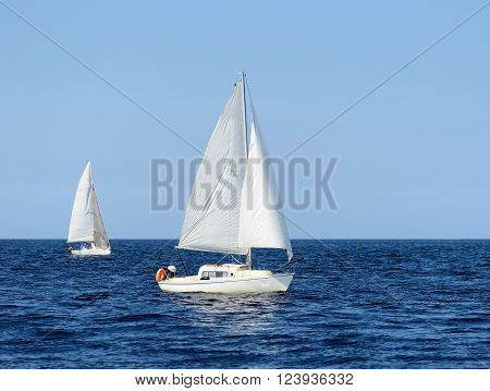 Two white sail yachts sailing in open Baltic sea on a clear sunny day