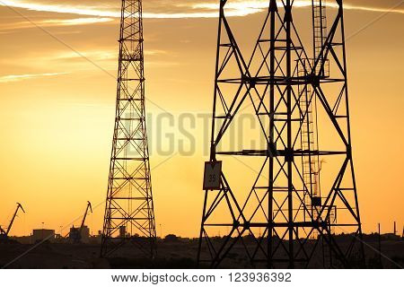 Electricity power line towers against yellow sunset sky. Industrial landscape.