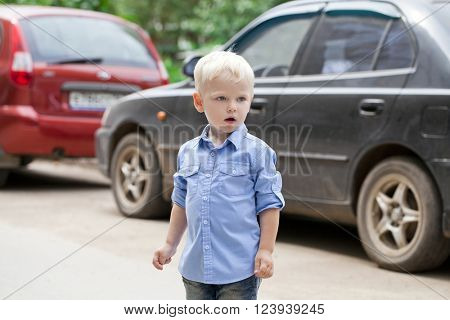 Portrait of blonde baby boy in blue shirt on summer street city