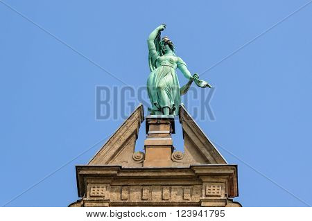 TORUN, POLAND - JULY 7, 2009: Statue of Fortune atop the gable of the Collegium Maximum building of the Nicolaus Copernicus University