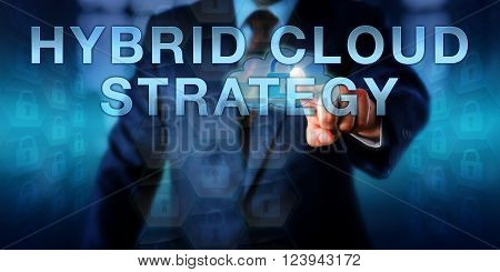 Enterprise user is touching HYBRID CLOUD STRATEGY on a virtual screen. Business metaphor and information technology concept for computer resource utilization both in the cloud and inhouse on premises.