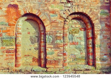Architectural details of ancient church wall - dead windows. Ancient wall made of plinfa - thin calcined brick. Old textured architectural background.