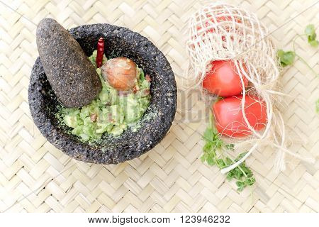 Photograph of smashed avocado guacamole in a traditional stone mexican molcajete ** Note: Soft Focus at 100%, best at smaller sizes
