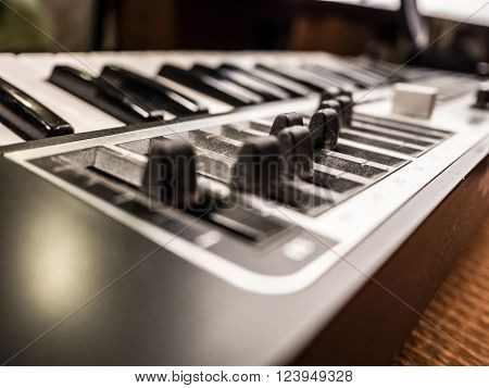 Macro view of black professional digital musical piano synthesizer with sliders. Background image of recording studio equipment. DJ using electronical device for making music.
