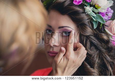The visagist is applying wedding makeup. Beautiful Bride.  Wedding makeup, wedding hairstyle