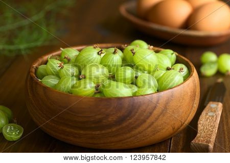 Raw gooseberries (lat. Ribes uva-crispa) in wooden bowl photographed on dark wood with natural light (Selective Focus, Focus on the upper gooseberries in the middle of the bowl)