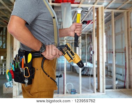 Builder handyman with drill and hammer.