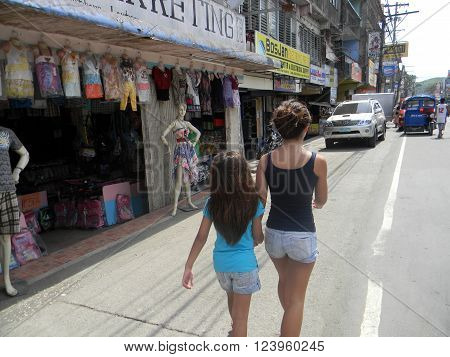 MAASIN, SOUTHERN LEYTE, PHILIPPINES / AUGUST 2, 2011: Two girls walk past a clothing store in downtown Maasin in Southern Leyte.