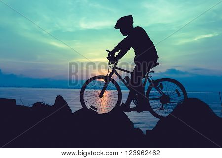 Silhouette of bicyclist riding the bike on a rocky trail at seaside, on colorful sunset sky background. Active outdoors lifestyle for healthy concept. Vintage style.