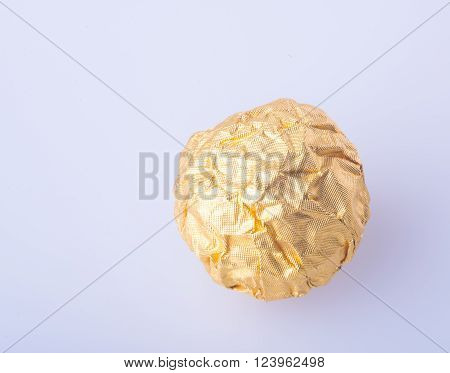 Chocolate Ball Or Chocolate Ball With Almond In A Gold Foil Paper On Background.