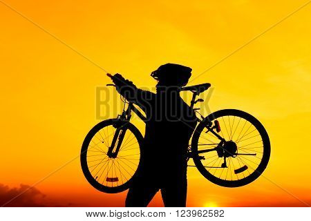 Silhouette of bicyclist carrying his bicycle on shoulder while walk against on colorful sunset orange sky background. Active outdoors lifestyle for healthy concept.