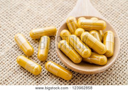 Herbal capsule. Alternative medical care on sack background.