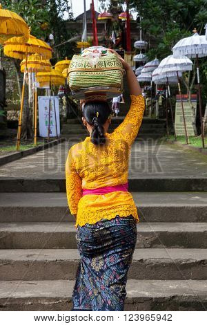 UBUD, INDONESIA - MARCH 2: Woman with basket on the head  walks up the stairs during the celebration before Nyepi (Balinese Day of Silence) on March 2, 2016 in Ubud, Indonesia.