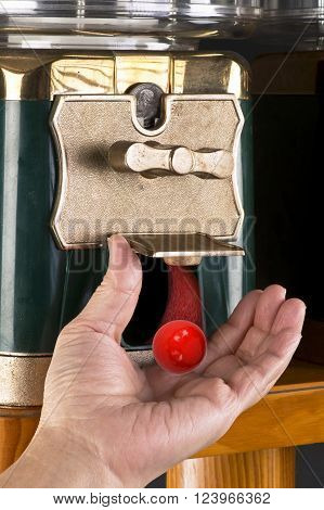 Gumball machine dropping red gumball ready to enjoy..