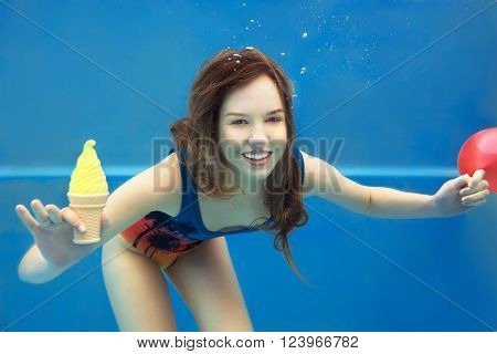 Beautiful smiling red hair girl eating yellow ice cream in the swimming pool underwater in summer