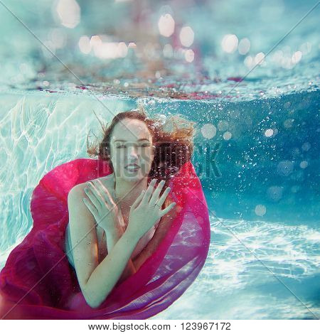 Smiling Young beautiful white woman in dress underwater in the swimming pool ** Note: Soft Focus at 100%, best at smaller sizes