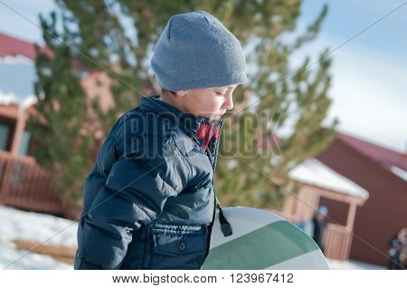 Little boy with grey toboggan carrying a sled looking down.