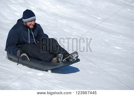 Man in toboggan on a sled on a snowhill going down laughing with copyspace.