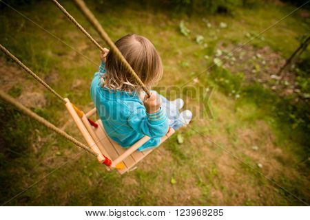 Child swinging on seesaw in backyard - above view ** Note: Shallow depth of field