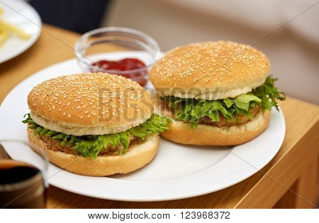 fast food and unhealthy eating concept - close up of hamburgers on table with ketchup at fast food restaurant or home