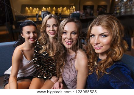 friends, bachelorette party, technology and holidays concept - happy smiling young pretty women taking selfie at night club