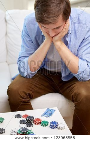 game, gambling and fail concept - losing man with playing cards and chips on table at home